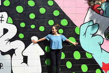 A girl poses in front of a wall covered with graffiti
